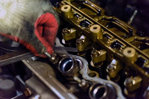 Auto mechanic repair engine in a car repair shop. Close up of cylinder head show rocker arm for maintenance check and adjust valve clearance